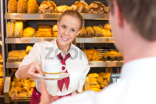 Shopkeeper in bakery handing out cup of tea or coffee