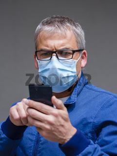 Mann mit Mundschutzmaske und Smartphone