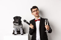 Handsome fancy man in glasses, raising glass of champagne and giving microphone to cute pug in party suit, celebrating and having fun, white background