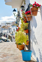 Empty pedestrian footpath and hanging flower pots on residential houses wall, charming small village of Mijas, Costa del Sol, Andalusia, Spain. Sunny day, famous travel destinations