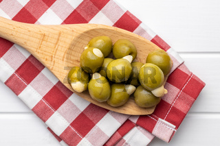 Pitted green olives stuffed with almonds on wooden spoon