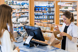 blonde female pharmacist puts medical supplies into a brown paper bag for a customer in a pharmacy