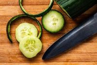 Cucumber sliced on wooden cutting board.