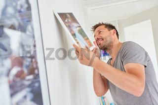 Mann befestigt einen Bilderrahmen im Wohnzimmer