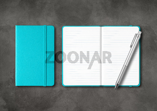 Aqua blue closed and open lined notebooks with a pen on dark concrete background