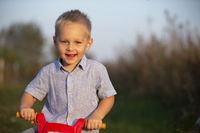 Cheerful little boy is holding a red rudder of a toy motorcycle and smiling for the camera.