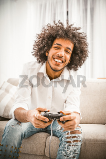 Cute gamer plays game console while sitting on couch. Charming shaggy Arab in ripped jeans and a white shirt toothy smiles enjoying the game. Front view. Toned image