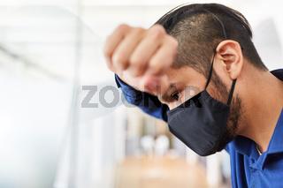 Geschäftsmann mit Mundschutz leidet an Burnout