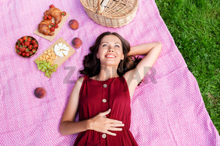 happy woman lying on picnic blanket at summer park