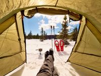 Man relaxing. Winter view from camping  tent entrance out