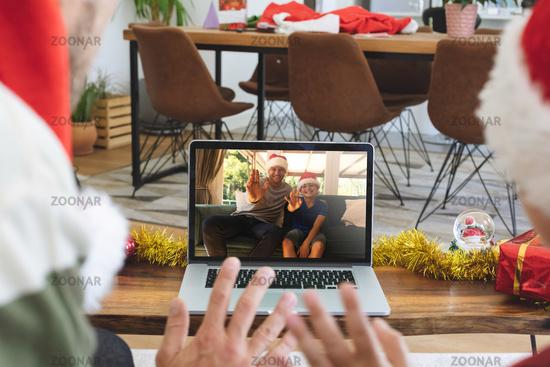 Rear view of man and son in santa hats waving while having a videocall with man and son in santa hat