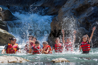 Happy preteens playing in the water of a small waterfall