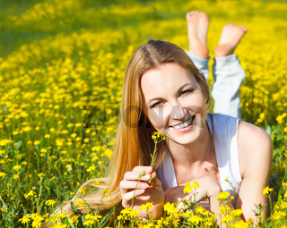 Young beautiful blond girl laying on the daisy flowers field. Outdoor portrait