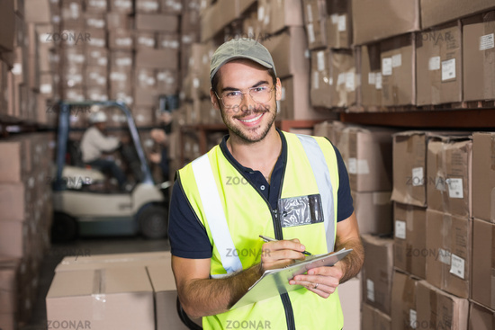 Warehouse worker smiling at camera with clipboard