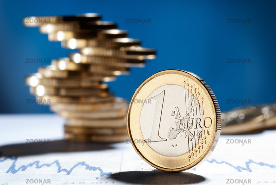 Euro coin with a stack of coins in the background