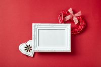 Photo frame and Valentines day hearts and decorations on red background.