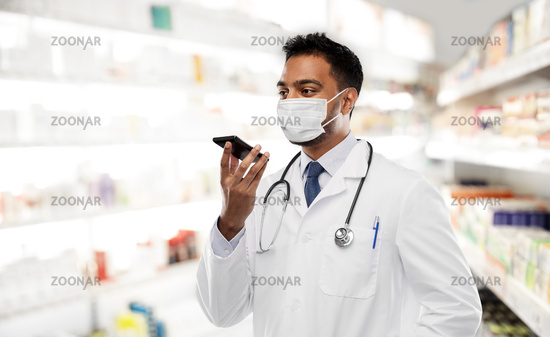 indian doctor in mask recording voice by cellphone