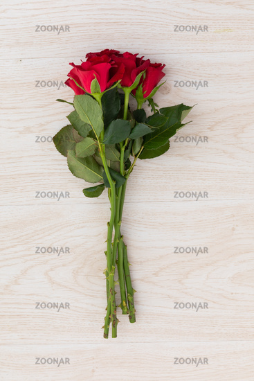 Bunch of red roses lying on wooden background