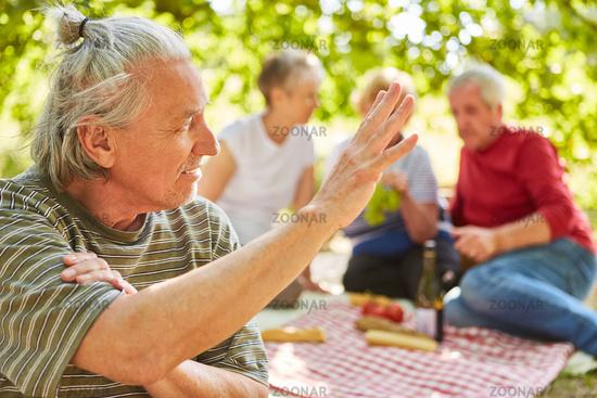 Senior macht mit Freunden ein Picknick im Park