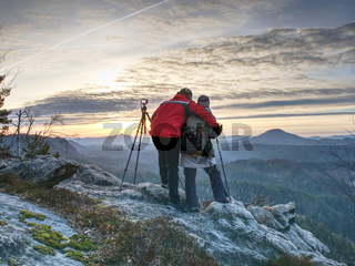 Two wildlife photographers at tripod with set  shinning camera