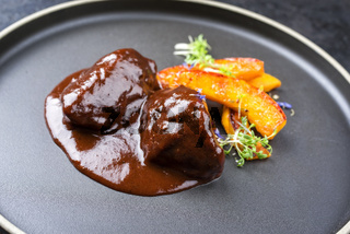 Traditional German braised beef cheeks in brown red wine sauce with pumpkin slices and herbs offered as closeup in a modern design plate