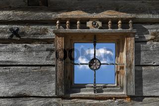 Altes Holzfenster einer Berghütte mit Himmel und Wolke