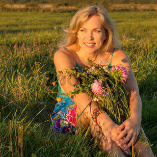 Beautiful woman sitting in a field with flowers an