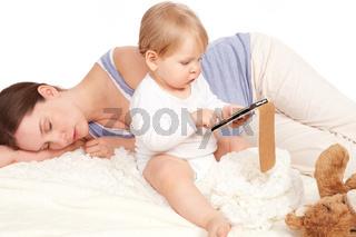 Kind spielt mit dem Smartphone waehrend Mutter schlaeft