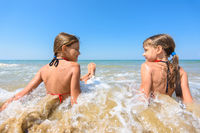 Children sit in water on a sandy beach and look at each other happily