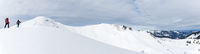 Senior couple is snowshoe hiking in alpine snow winter mountains panorama. Allgau, Bavaria, Germany.