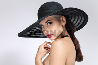 Elegant close-up portrait of young woman with stylish black sun hat