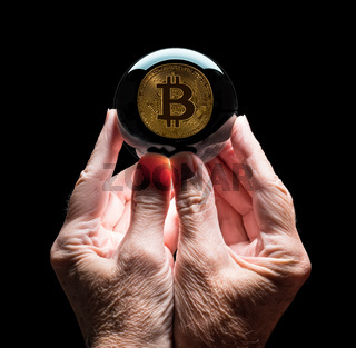 Crystal glass forecasting ball held by mans hands predicting future price of bitcoin