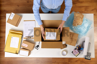 woman packing parcel boxes at post office