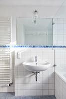 Waschbecken mit Spiegel im Bad neben Röhrenheizkörper