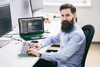 Serious computer programmer developer working in IT office, sitting at desk and coding, working on a project in software development company or startup.