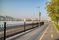 Sidewalk along Danube river with view to Margaret Bridge, Budapest.