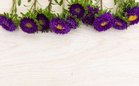 Purple flowers in a row at the top on wooden background
