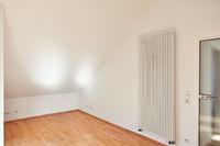 Leerer Raum in Dachgeschosswohnung mit Heizkörper