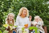 Mutter mit Kindern im Herbst im Garten
