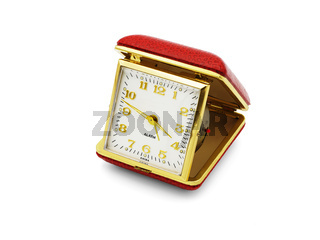 A old red folding travel alarm clock on white background
