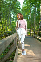 A beautiful woman posing on a wooden bridge in a Park