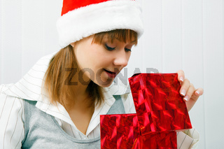 Attractive girl opens a Christmas present