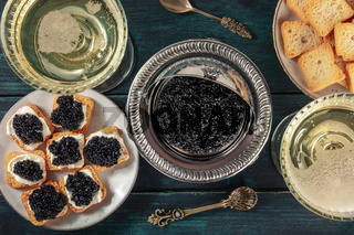 Black caviar with champagne in vintage coupe glasses, with toasts, a flat lay, top shot