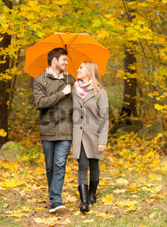 smiling couple with umbrella in autumn park