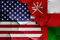 flags of USA and Oman painted on cracked wall