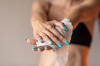 Old woman gently cleaning hands with wet wipes