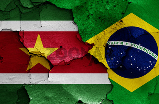 flags of Suriname and Brazil painted on cracked wall