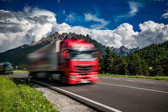 Fuel truck rushes down the highway in the background the Alps. Truck Car in motion blur.