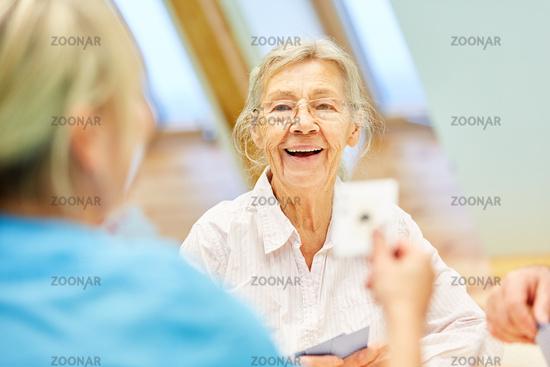 Seniorin im betreuten Wohnen spielt Karten