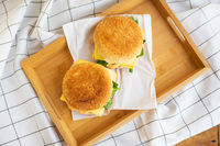 Two hamburgers lie on a wooden tray with a white napkin, close-up, top view.